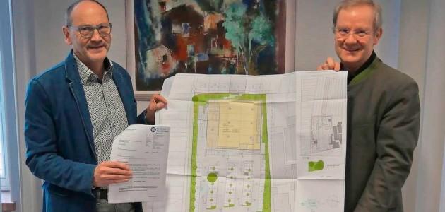 Die Baugenehmigung für den Lebensmittelmarkt ist erteilt. Bürgermeister Markus Fuchs und Geschäftsführer Matthias Engel mit dem Bauplan. Foto: Gemeinde Schiffweiler/Kaiser